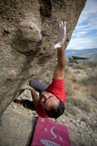 climber reaching for a hold on a boulder